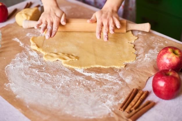 Hände arbeiten mit teigzubereitungsrezeptbrot. weibliche hände, die teig für apfelkuchen machen. frauenhände rollen den teig. mutter rollt teig auf dem küchenbrett mit einem nudelholz