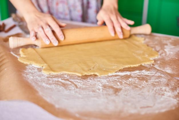 Hände arbeiten mit teigzubereitungsrezeptbrot. weibliche hände, die teig für pizza machen. frauenhände rollen den teig. mutter rollt teig auf dem küchenbrett mit einem nudelholz