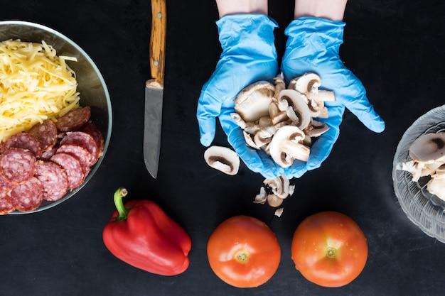 Hände auf blauen silikonhandschuhen halten geschnittene pilze, draufsicht