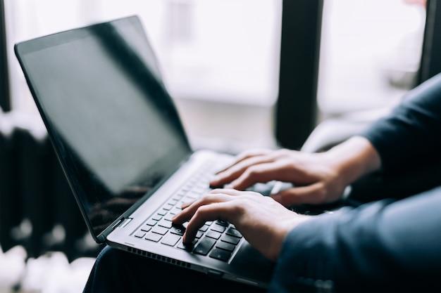 Hände auf der tastatur des laptops schreiben text.