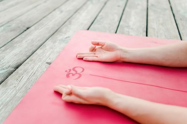 Hände auf einer yogamatte mit einem om-mantrasymbol