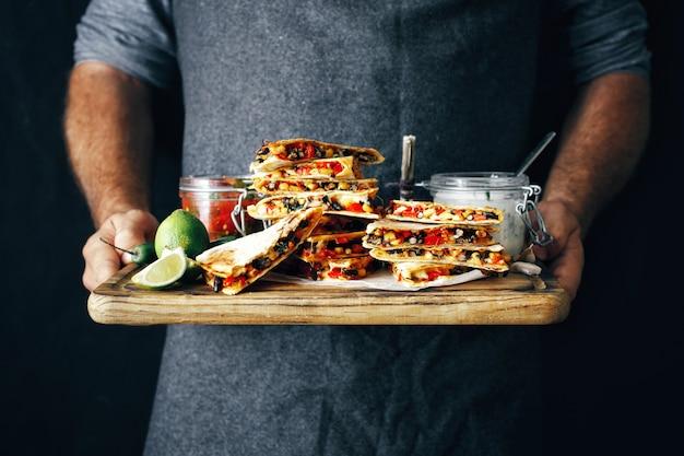 Hände bemannen vegetarischen aperitifquesadillagemüsekäse des schneidebretts
