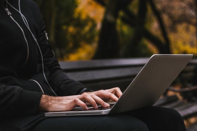 Hände beschäftigt auf einem laptop im park zu tippen