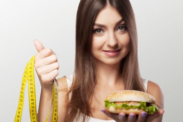 Hände bieten einem apfel gesunde nahrung an und backen ungesunde nahrung miteinander zusammen.