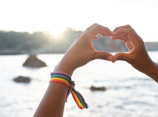Hände bilden ein herz am strand