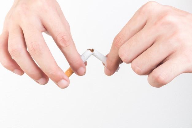 Hände brechen zigarette lokalisiert auf weißem hintergrund