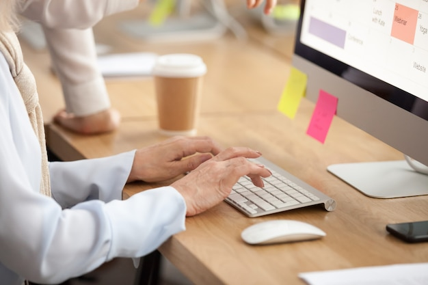 Hände der älteren frau, die auf der tastatur arbeiten an computer, nahaufnahme schreiben