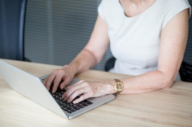 Hände der älteren geschäftsfrau tippen auf laptop
