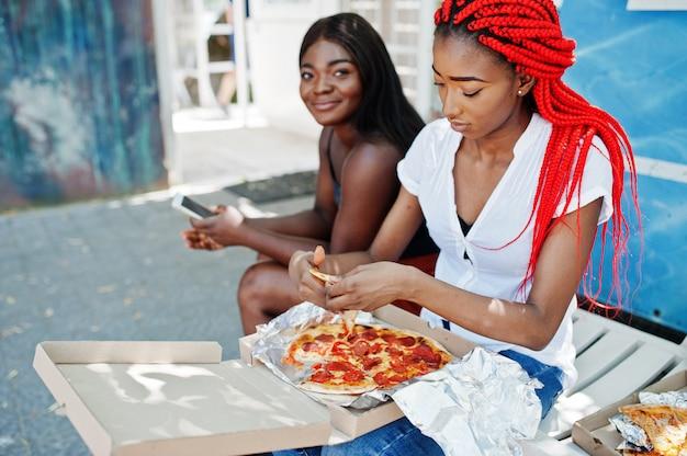 Hände der afroamerikanerfrau mit pizza.