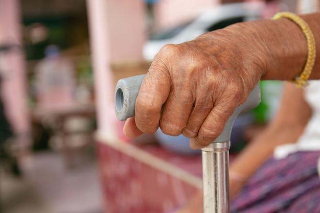 Hände der alten frau asien mit einem stockspazierstock