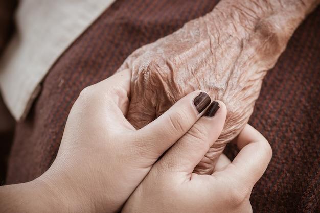 Hände der asiatischen jugendfrau, die ältere großmutter hält, hände geknitterte haut