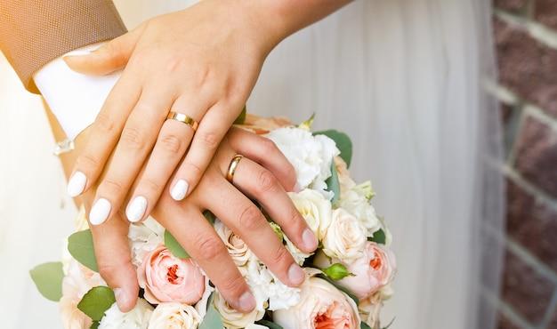 Hände der braut und des bräutigams auf dem hochzeitsstrauß. goldringe an den fingern der jungvermählten. getöntes foto.