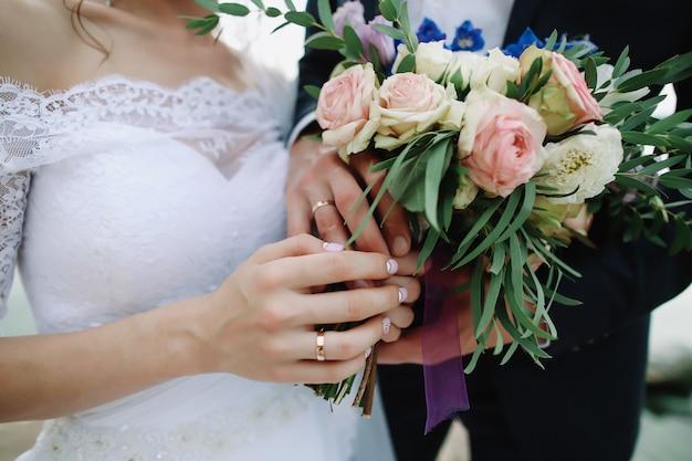 Hände der braut und des bräutigams, die einen hochzeitsstrauß halten