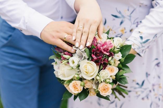 Hände der braut und des bräutigams mit eheringen liegen auf dem hochzeitsblumenstrauß von hellen blumen. ehe seit vielen jahren