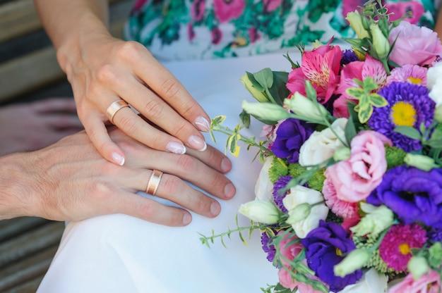 Hände der braut und des bräutigams mit ringen und hochzeitsblumenstrauß