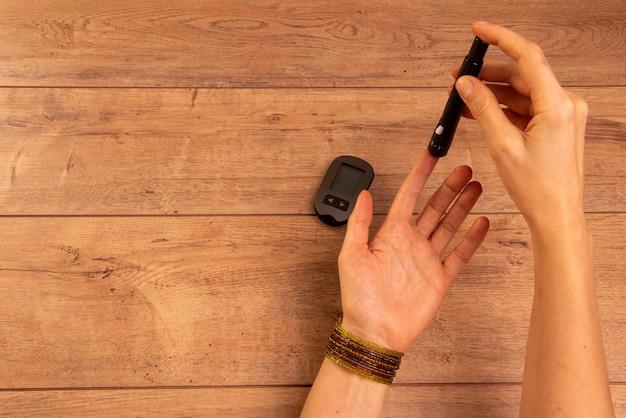 Hände der diabetischen frau, die geräte verwendet, um blutzucker zu messen.