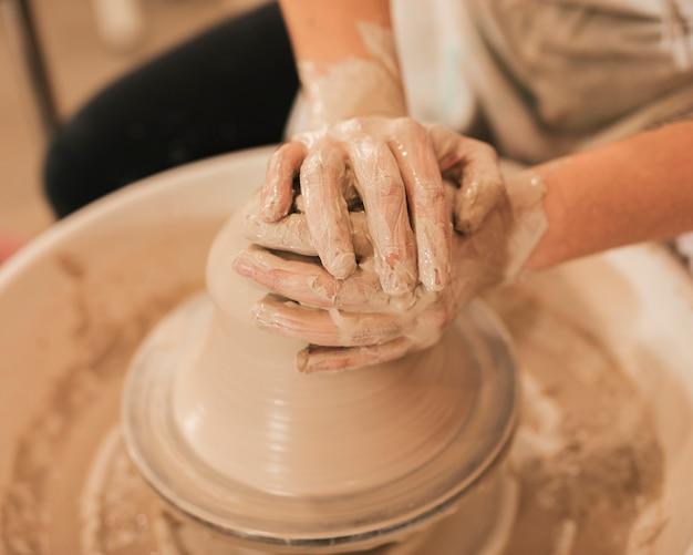 Hände der frau bei der herstellung der lehmschüssel auf töpferscheibe