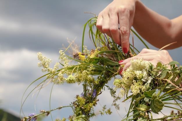 Hände der frau den kranz von wildflowers auf einem blauen bewölkten himmel in handarbeit machend