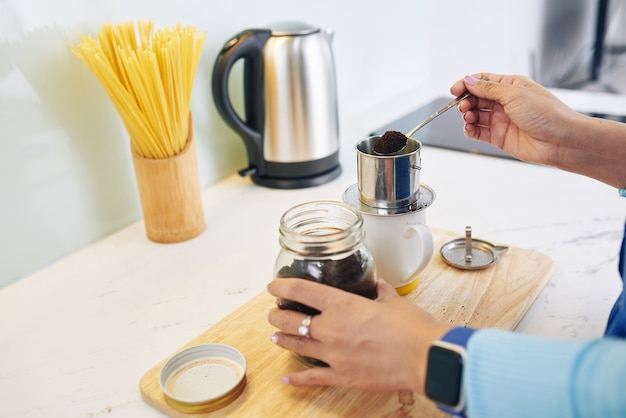 Hände der frau, die am morgen kaffee zu vietnamesischen art zu hause macht