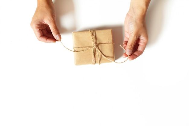 Hände der frau, die ein geschenk einwickeln