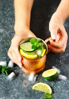 Hände der frau, die einen kupfernen becher limonade mit minze anhalten
