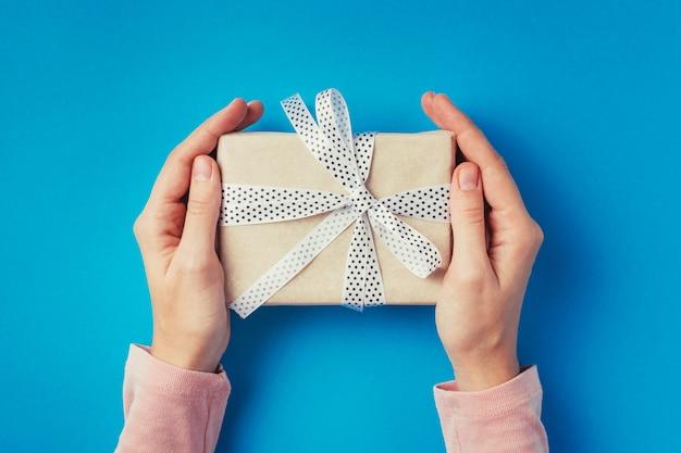 Hände der frau, die geschenkbox auf blauem hintergrund, draufsicht halten