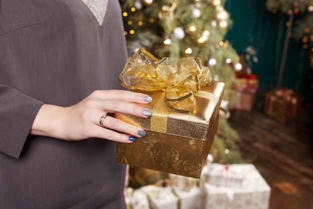 Hände der frau, die goldgeschenkbox halten. weihnachten, neujahr, geburtstag.