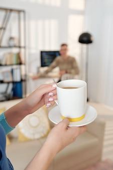 Hände der frau, die ihrem mann, der wegen einer pandemie zu hause am computer arbeitet, eine tasse kaffee bringen