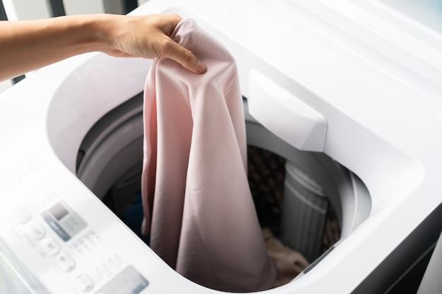 Hände der frau, die in der eigentumswohnung kleidung in die waschmaschine legt. wäschekonzept. ansicht von oben