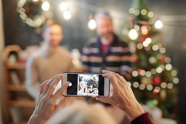 Hände der frau, die smartphone mit foto der glücklichen liebevollen familie auf seinem bildschirm hält, während foto durch festlichen tisch nehmen