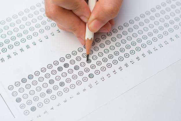 Hände der frau, die standardisiertes testformular ausfüllen
