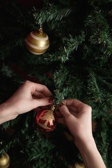 Hände der frau, die weihnachtsbaum verziert