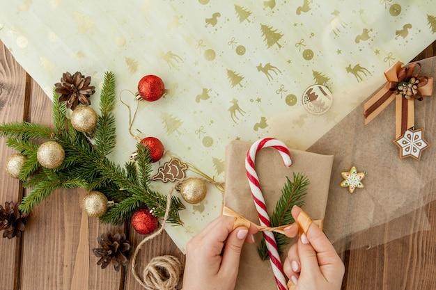 Hände der frau, die weihnachtsgeschenk einwickeln