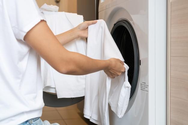 Hände der frau, die weiße kleidung in die waschmaschine in der küche zu hause lädt. wäschekonzept.