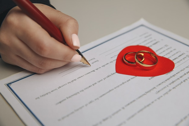 Hände der frau, ehemann, der scheidungsurteil unterzeichnet, auflösung, heirat annulliert, dokumente zur rechtlichen trennung