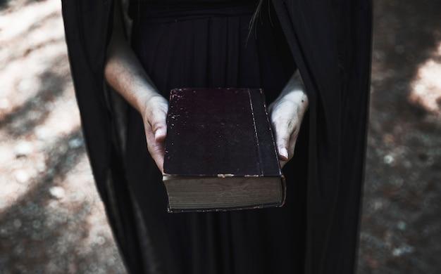 Hände der frau im schwarzen kleid, das altes buch hält