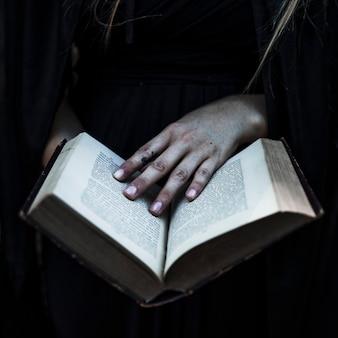 Hände der frau in der schwarzen kleidung, die geöffnetes buch hält