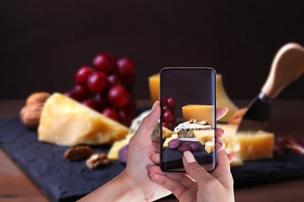 Hände der frau mit dem smartphone, der foto macht sortierte käse. dunkler und launischer stil.