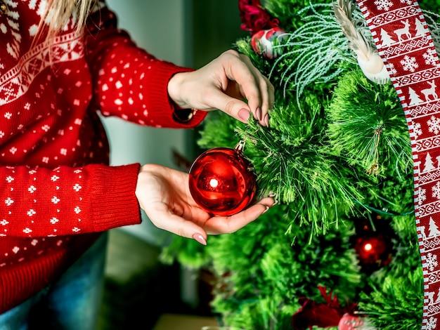 Hände der frau oder des mädchens schließen oben einen weihnachtsbaum für weihnachten
