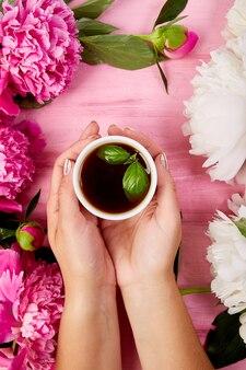 Hände der frau und eine tasse tee halten