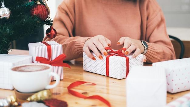 Hände der frau weihnachts- und neujahrsgeschenkbox verzierend.
