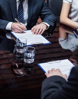 Hände der geschäftsleute, die auf der sitzung sitzen und den vertrag unterzeichnen.