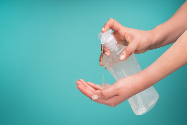 Hände der gesunden jungen frau, die antibakterielles gel anwenden, um krankheiten vorzubeugen, zerstören das coronavirus mit kopierraum