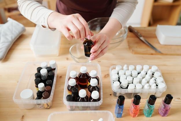 Hände der handwerkerin, die kleine flasche mit gewählter aromatischer essenz über plastikbehältern auf holztisch öffnet