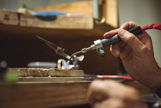 Hände der handwerkerin mit lötlampe