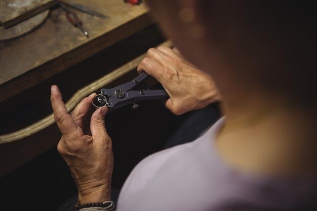 Hände der handwerkerin mit zange