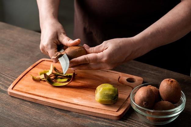 Hände der hausfrau, die frische kiwi über schneidebrett durch küchentisch schält, während sie sie für das schneiden und trocknen für den winter vorbereiten