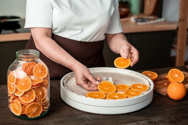 Hände der hausfrau, die orangenscheiben auf plastikschalen des speisetrockners legt, während kandierte zitrusfrüchte für den winter in der küche gemacht werden