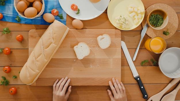 Hände der jungen asiatischen köchin halten messer, das vollkornbrot auf holzbrett schneidet