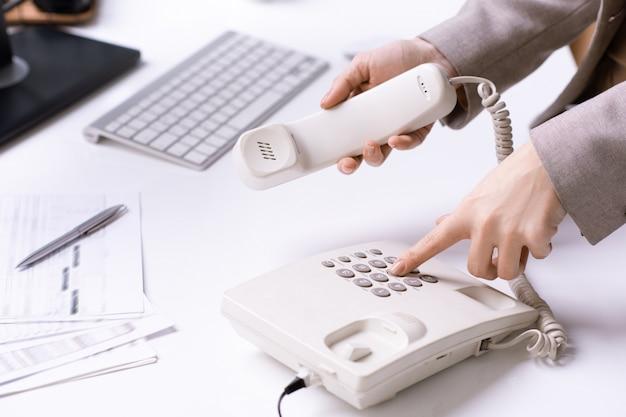 Hände der jungen bürosekretärin, die telefonnummer wählt und empfänger hält, während einer der kunden durch arbeitsplatz anruft